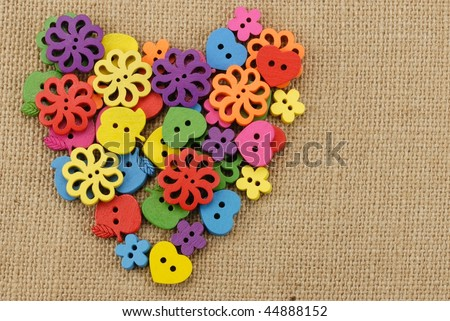 Colorful wooden buttons arranged in heart shape on handwoven cotton fabric. - stock photo