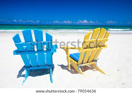 Colorful wooden chairs on beach at Caribbean coast - stock photo