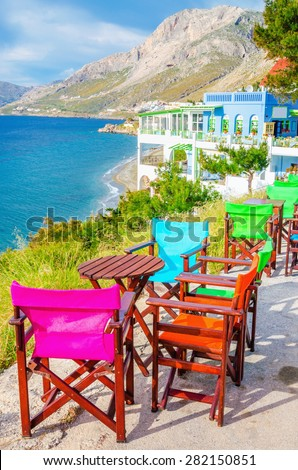 Colorful wooden chairs with view on sea bay on Greek Island, Greece - stock photo