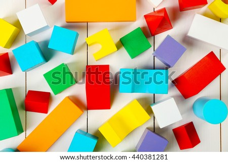 Colorful wooden children's building blocks on white wooden background - stock photo
