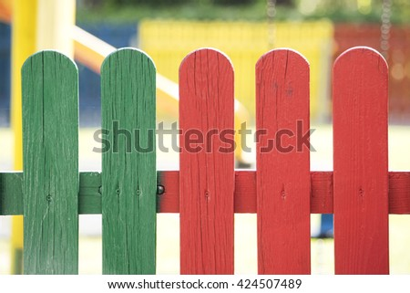 Colorful wooden fence boards. Blurred playground in the background. Red and green colors - stock photo
