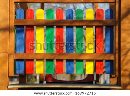 Colorful wooden fence on kids playground - stock photo