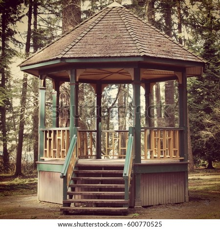 Colorful wooden gazebo with faded paint, singled roof with moss growing and surrounded by trees.