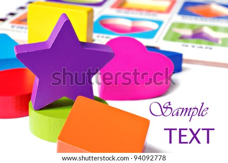 Colorful wooden geometric shaped puzzle pieces on white background with puzzle board in  background.  Macro with shallow dof. - stock photo
