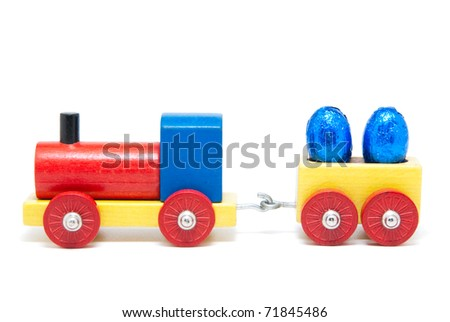 Colorful wooden model railway with Easter eggs on goods wagons, isolated