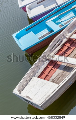 Colorful wooden rowboats anchor at the pier. - stock photo