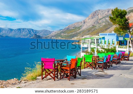 Colorful wooden tables and chairs with view on sea bay on Greek Island, southern Greece - stock photo