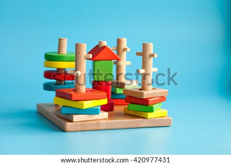 Colorful wooden toy building blocks with toys on a blue background - stock photo