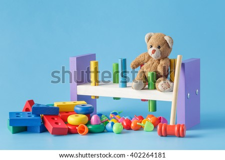 Colorful wooden toy building blocks with toys on blue - stock photo