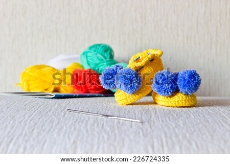 Colorful wool baby bootees with wool and knitting needles on white background - stock photo