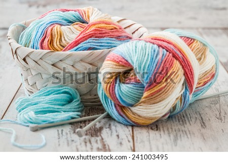 Colorful woolen knitting yarns in white basket on white wooden table - stock photo