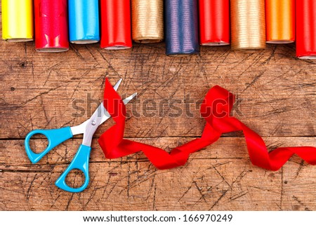 Colorful wrapping paper rolls with scissors and red ribbon, Christmas concept  - stock photo