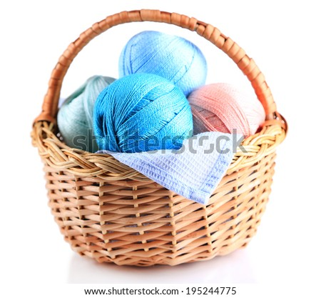 Colorful yarn balls for knitting in wicker basket, isolated on white