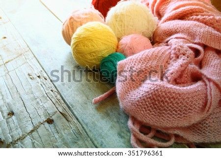 colorful yarn balls of wool on wooden table, old faded vintage style filtered photo  - stock photo