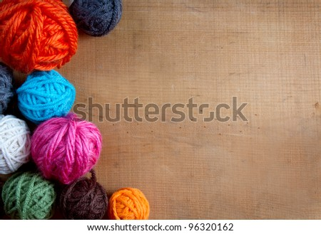 Colorful yarn balls on a wooden background room for copy space - stock photo