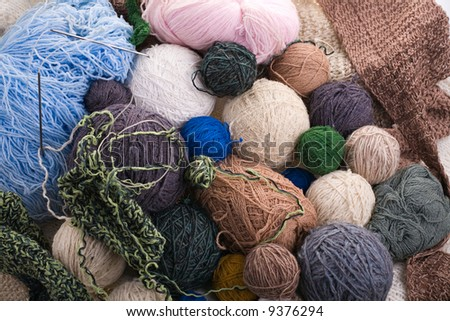 colorful yarn balls with needles and knitting as background