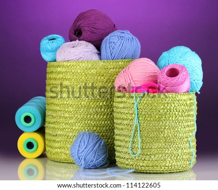 Colorful yarn for knitting in green basket on purple background