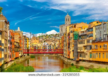 Colorful yellow and orange houses and Eiffel Bridge, Old fish stalls, reflected in water river Onyar, in Girona, Catalonia, Spain. Saint Mary Cathedral at background. - stock photo