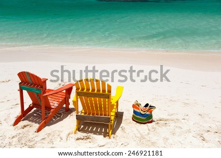 Colorful yellow and orange lounge chairs at tropical beach in Caribbean with beautiful turquoise ocean water and white sand - stock photo