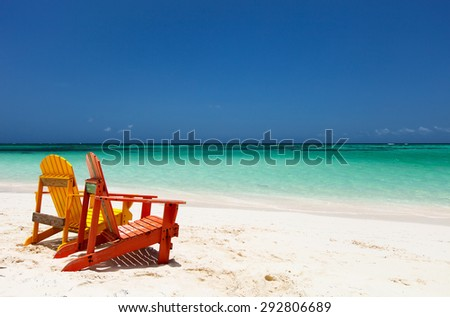 Colorful yellow and orange lounge chairs at tropical beach in Caribbean with beautiful turquoise ocean water, white sand and blue sky - stock photo