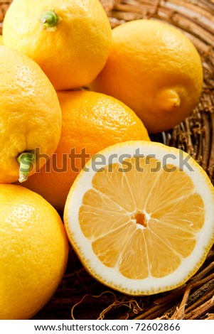 Colorful yellow lemons piled in a natural vine basket are ready for making summer lemonade - stock photo