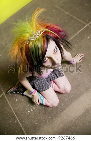 Colorful young punk girl sitting in front of a green wall - stock photo