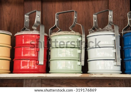Colorful zinc tiffin on wooden shelves - stock photo
