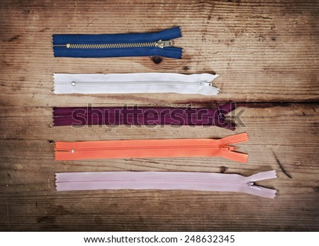 Colorful zippers in different sizes over wooden background - stock photo
