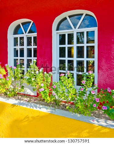 Colorfull contemporary, residential two windows on the red wall with the flowers. Mediterranean, Caribbean style. - stock photo