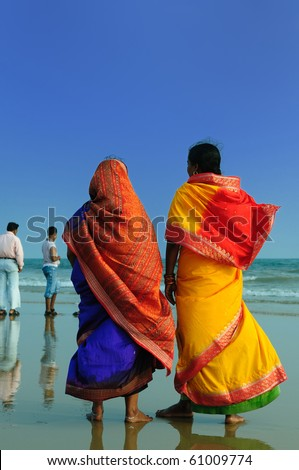 Colorfull Indian woman with sari walking on a beach in Orissa, India - stock photo
