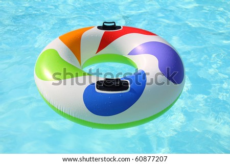 colorfull swim ring floating on a blue swimming pool - stock photo