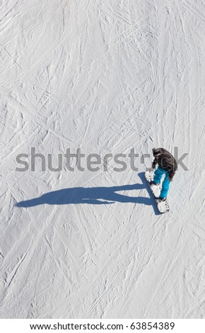 Colorfully dressed snowboarder from above on a snow slope riding his snowboard.