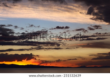 Colorfully lit evening sky with dark clouds shortly after sunset over Lake Titicaca viewed from the small tourist town of Copacabana in Bolivia