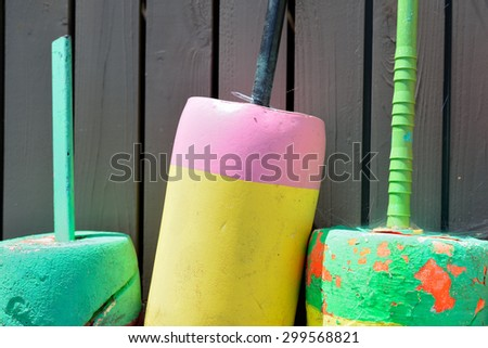 Colorfully painted lobster floats showing their age after use in salt water - stock photo