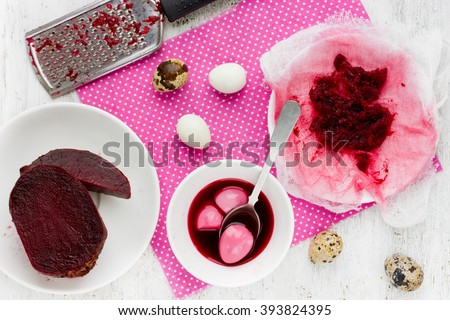 Coloring Easter Eggs from natural beet juice in pink color. Food concept for Easter holidays. Cooking process and ingredients on white background top view - stock photo