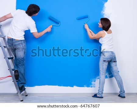 Coloring the wall in blue by young couple in casuals - horizontal