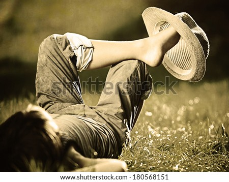 Colorized filtered image of carefree boy lying on grass - stock photo