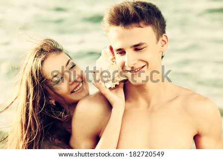 Colorized vintage outdoor portrait of beautiful girl putting shell to muscular guy's ear - stock photo