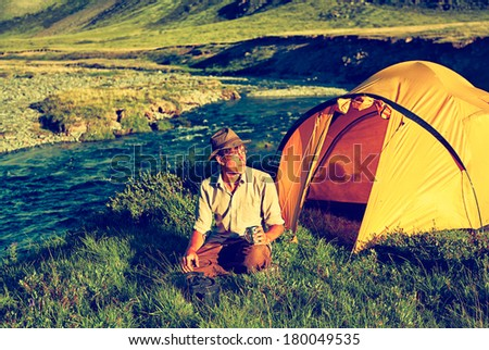 Colorized vintage outdoor portrait of tourist in Altai camp sitting near the river and drinking tea - stock photo