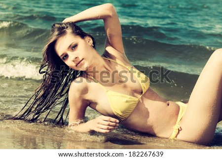 Colorized vintage outdoor portrait of Young beautiful slavonic girl in yellow bikini posing on the beach