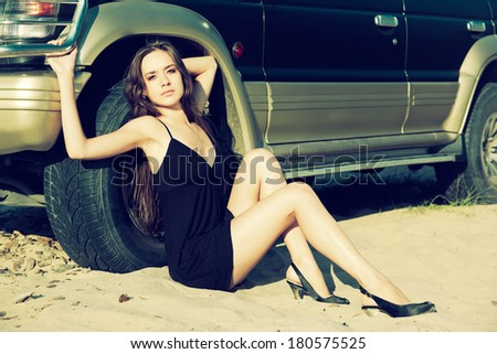 Colorized vintage outdoor portrait of Young beautiful slavonic girl sitting on the sand in black dress near the off-roader's wheel.