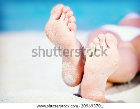 Colorized vintage photo of woman's feet on the white sand near the sea. - stock photo
