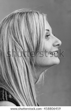 colorless portrait in profile of attractive caucasian smiling woman on gray background, studio shot - stock photo
