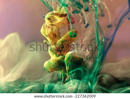 Colors dropped into liquid and photographed while in motion. Ink swirling in water. Cloud of silky ink in water. Colorful ink in water, an abstract banner. Yellow, green and pink ink. - stock photo