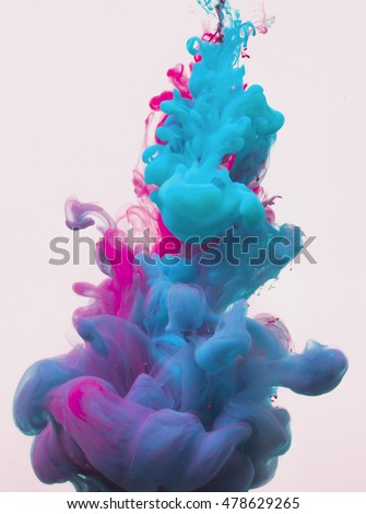 Colors dropped into liquid and photographed while in motion. Ink swirling in water. Cloud of silky ink in water isolated on white background. Colorful ink in water, an abstract banner. Color drop.