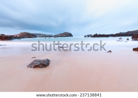 Colors of the clouds at the sunrise on the beach - stock photo