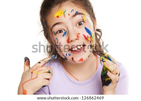 colors stained happy and smiling little girl pointing a finger on white background