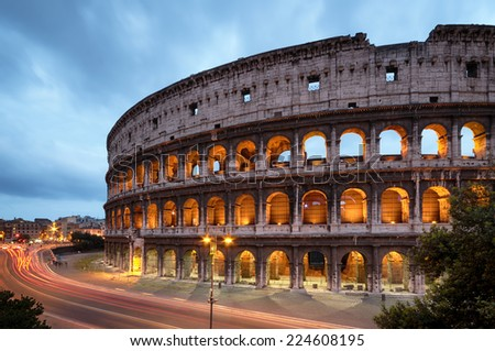 Colosseum at night with colorful blurred traffic lights. Rome - Italy.