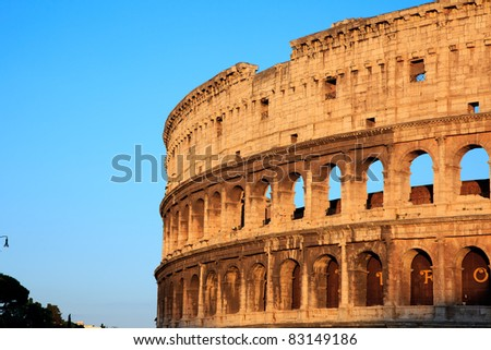 colosseum in Rome, capital of italy, at sunset with beautiful yellow colored stones and blue sky