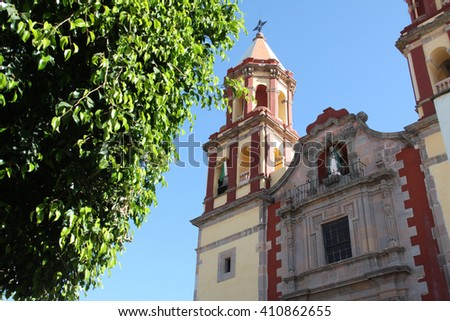 Colour image of a Catholic Church in Queretero Mexico. Blue sky in background and green tree in foreground.  There are two bell towers. Statue of Virgin Mary visible. - stock photo